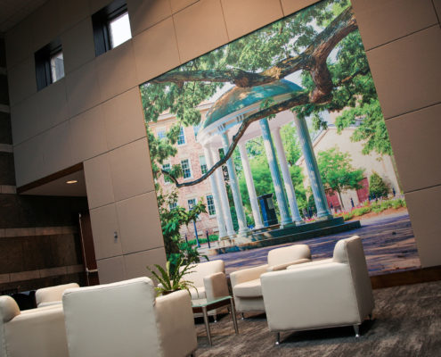 A seating area features a picture of the Old Well at UNC-Chapel Hill