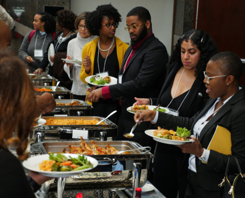Conference attendees serve themselves lunch via a buffet