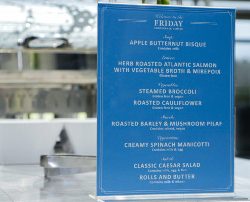 A menu greets attendees as they queue for lunch